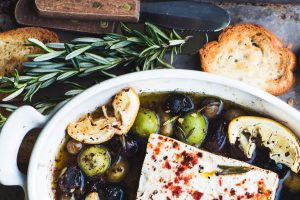 Baked feta cheese with olives, lemon, and rosemary with toasted bread on a tray with toasted bread