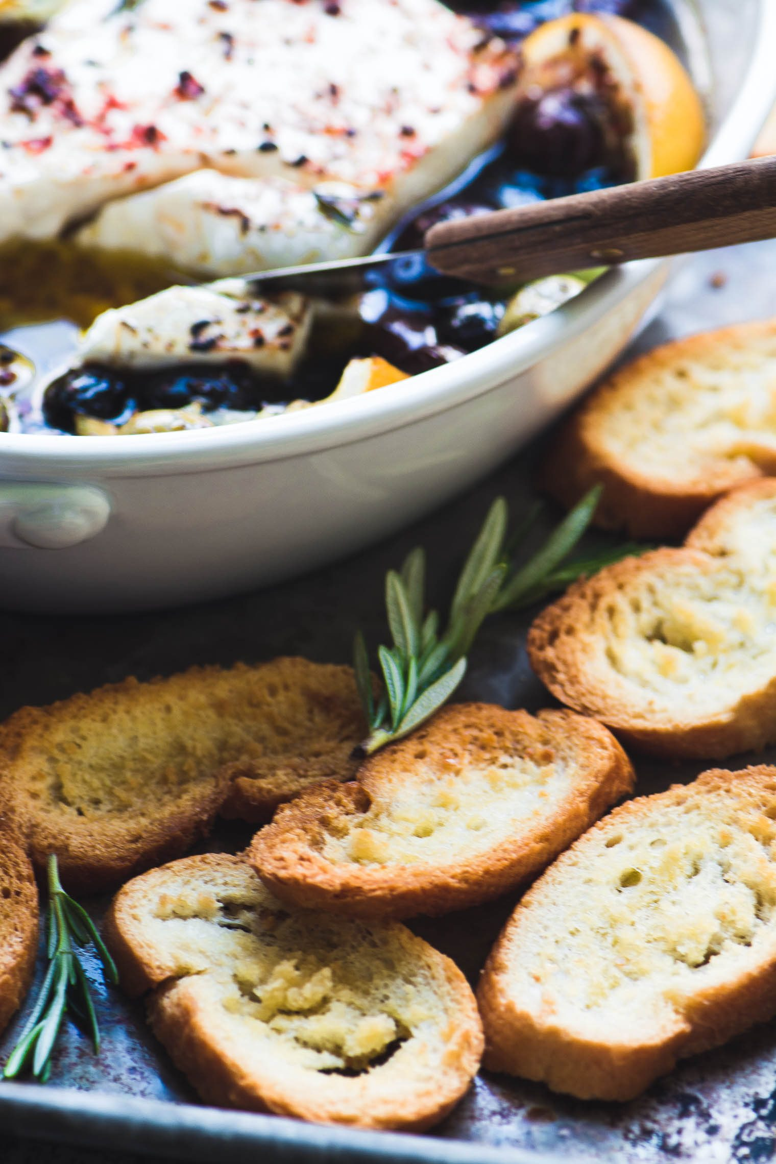 Baked feta cheese with olives, lemon, and rosemary with toasted bread