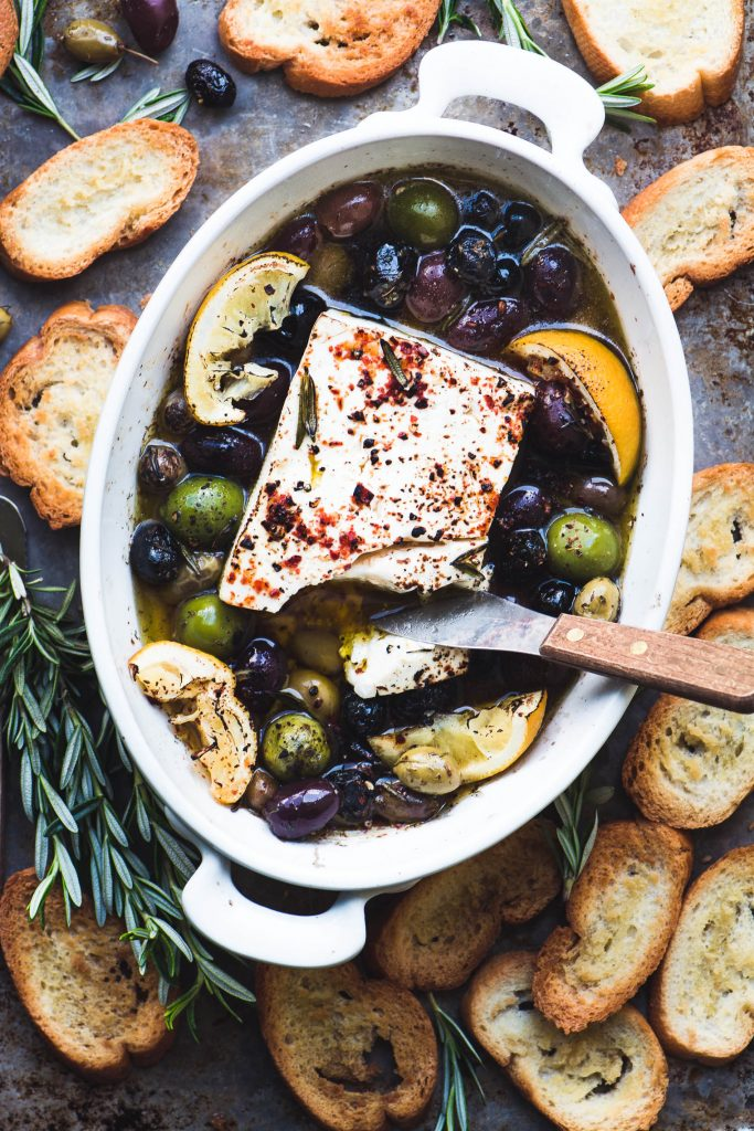 overhead shot of baked feta cheese with olives, lemon, and rosemary