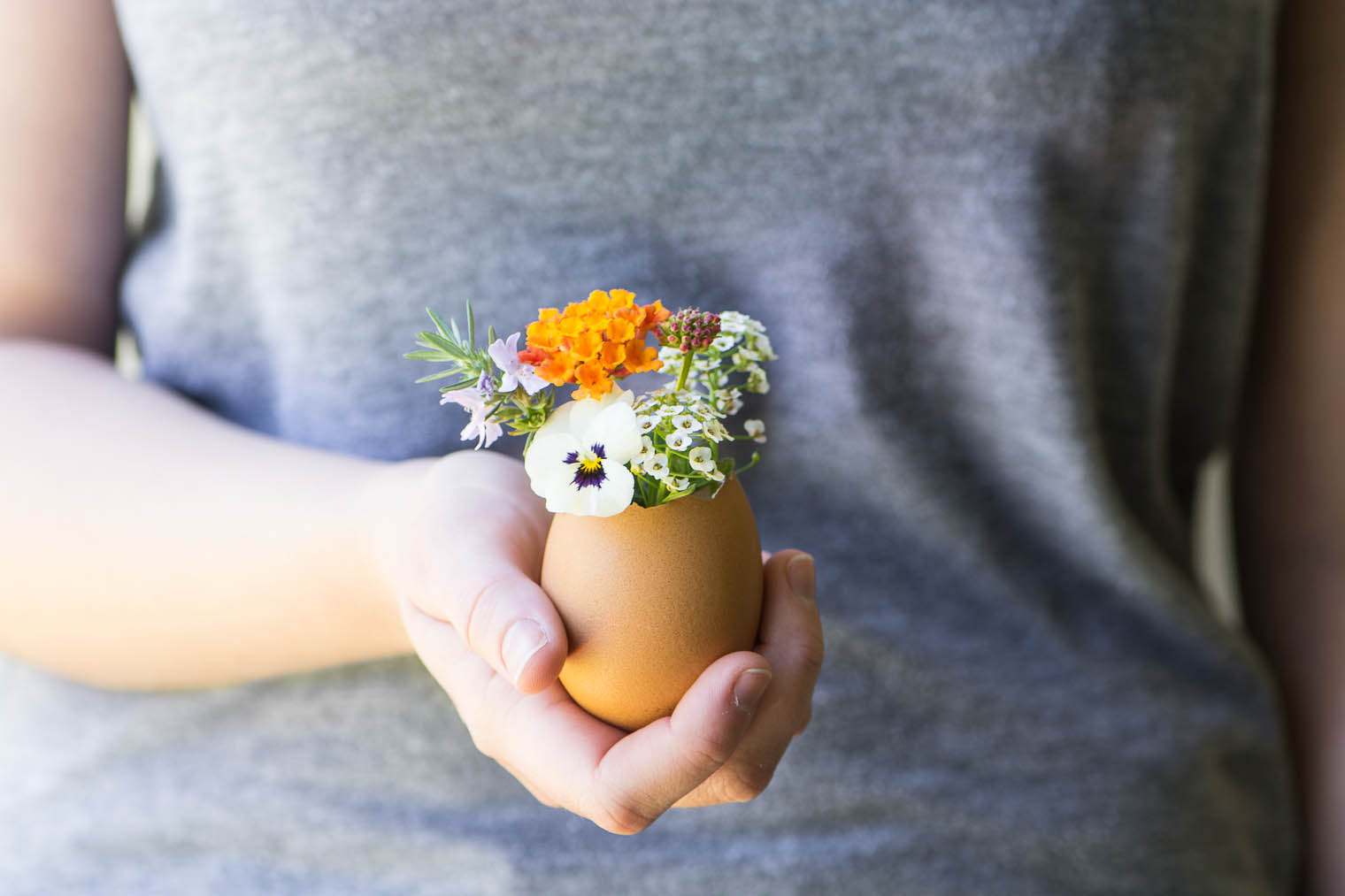 A hand holding an eggshell vase with flowers.