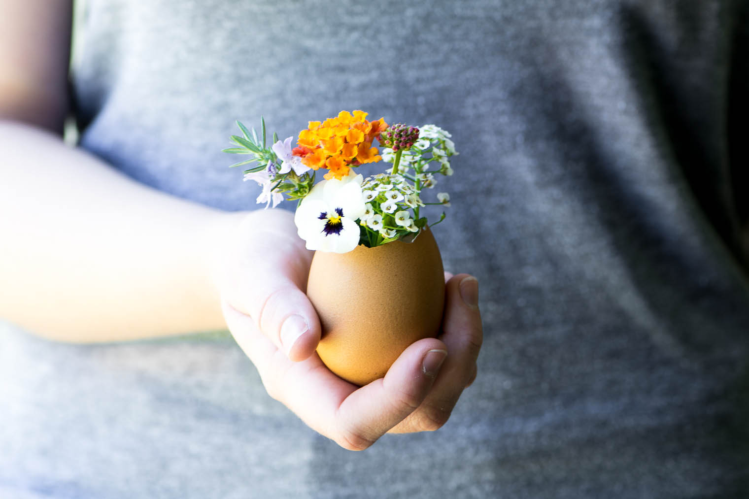 A mini bud vase made from an eggshell, filled with flowers