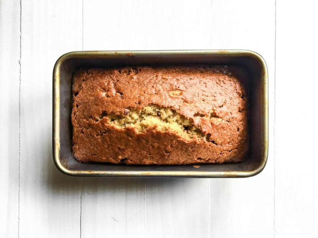 one banana banana bread cooling in loaf pan on white board