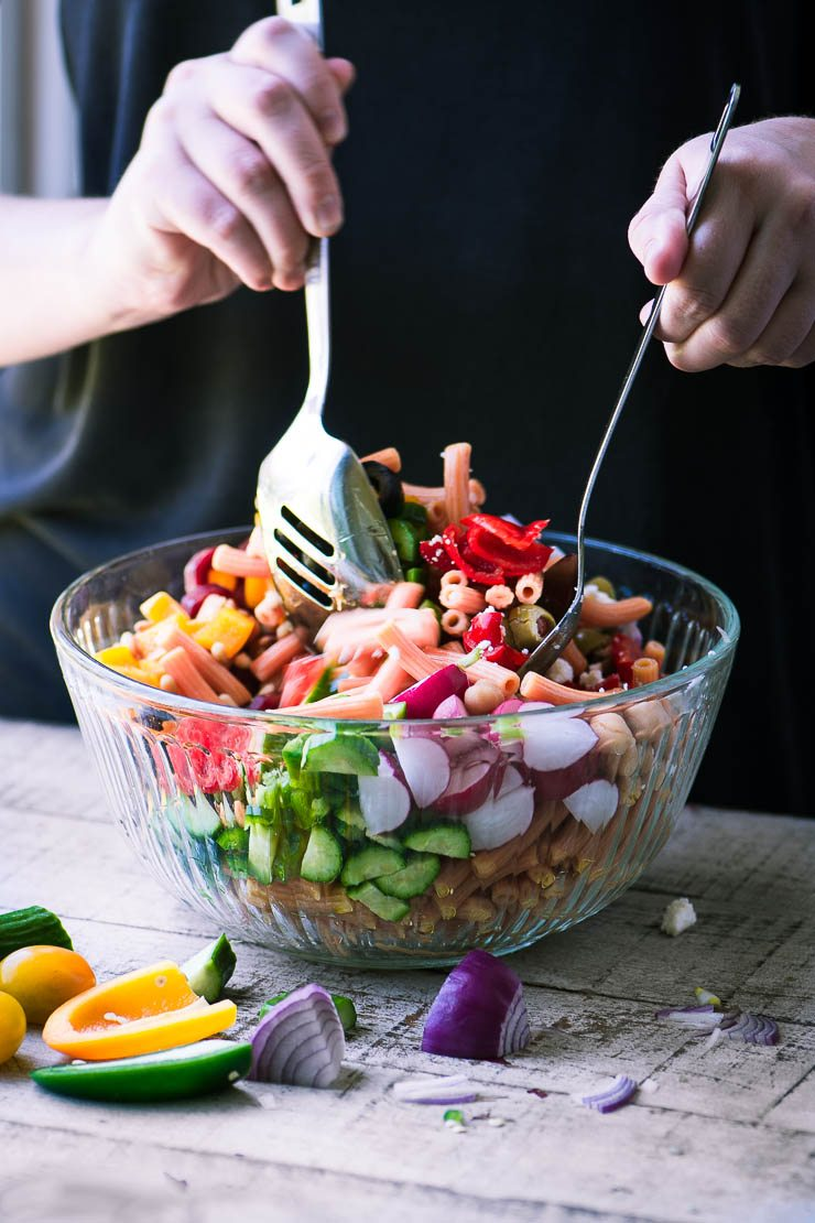 Tossing a colorful gluten free pasta salad in a glass bowl.