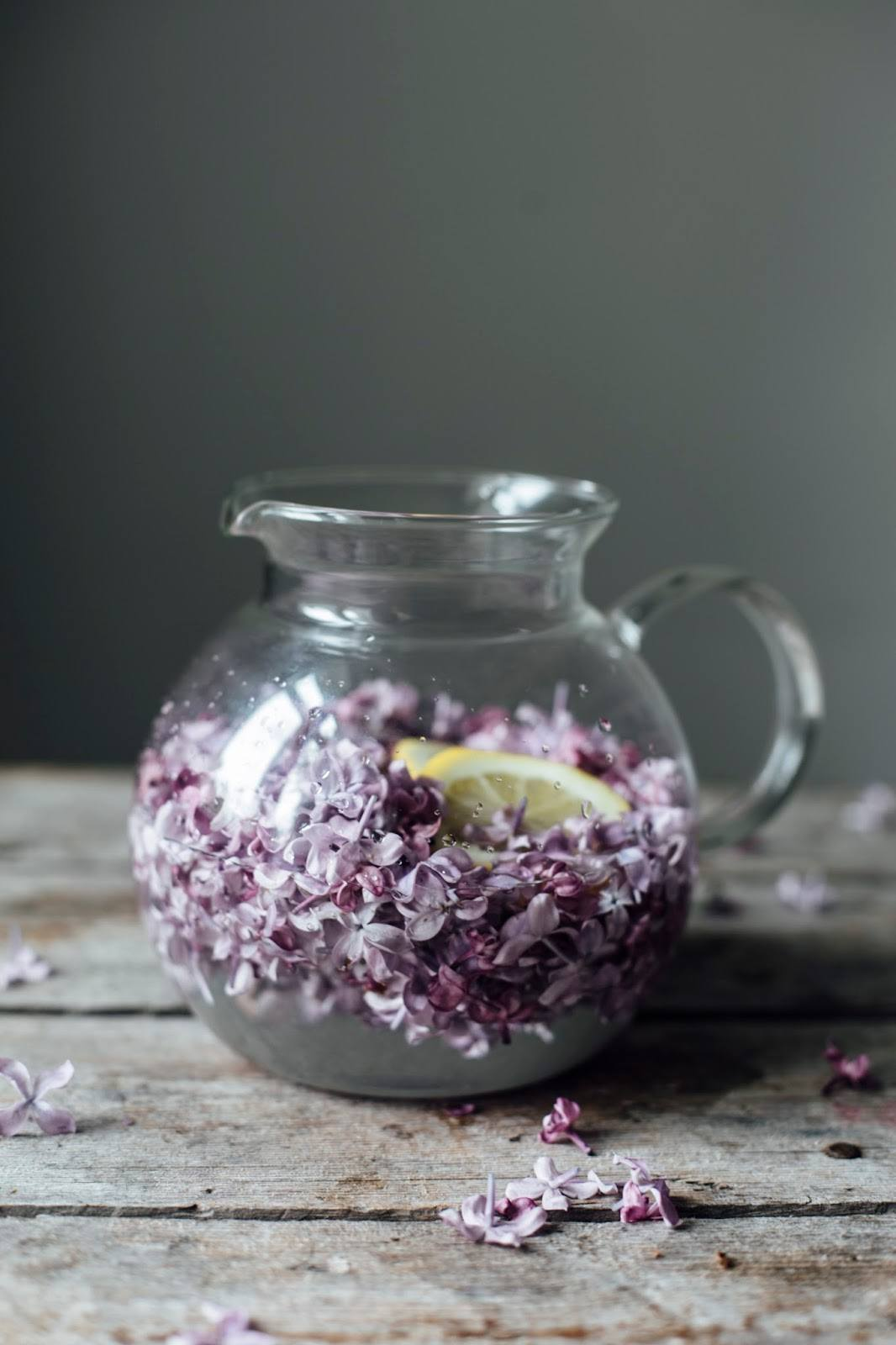 Lilac syrup in a glass pitcher.