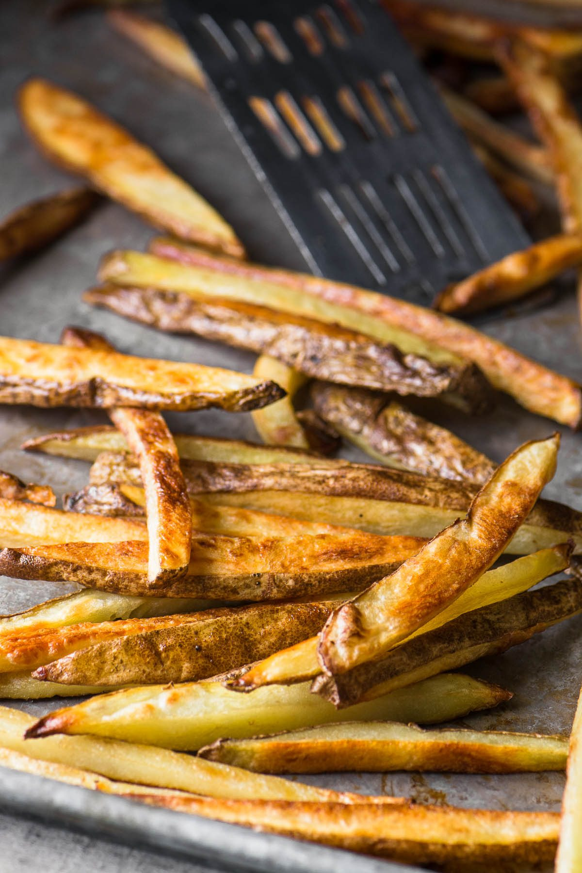 Baked french fries on a baking tray with spatula