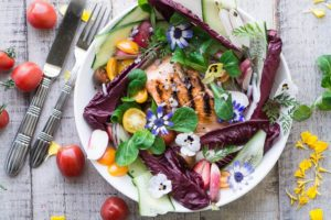 overhead shot of grilled salmon salad with edible flowers