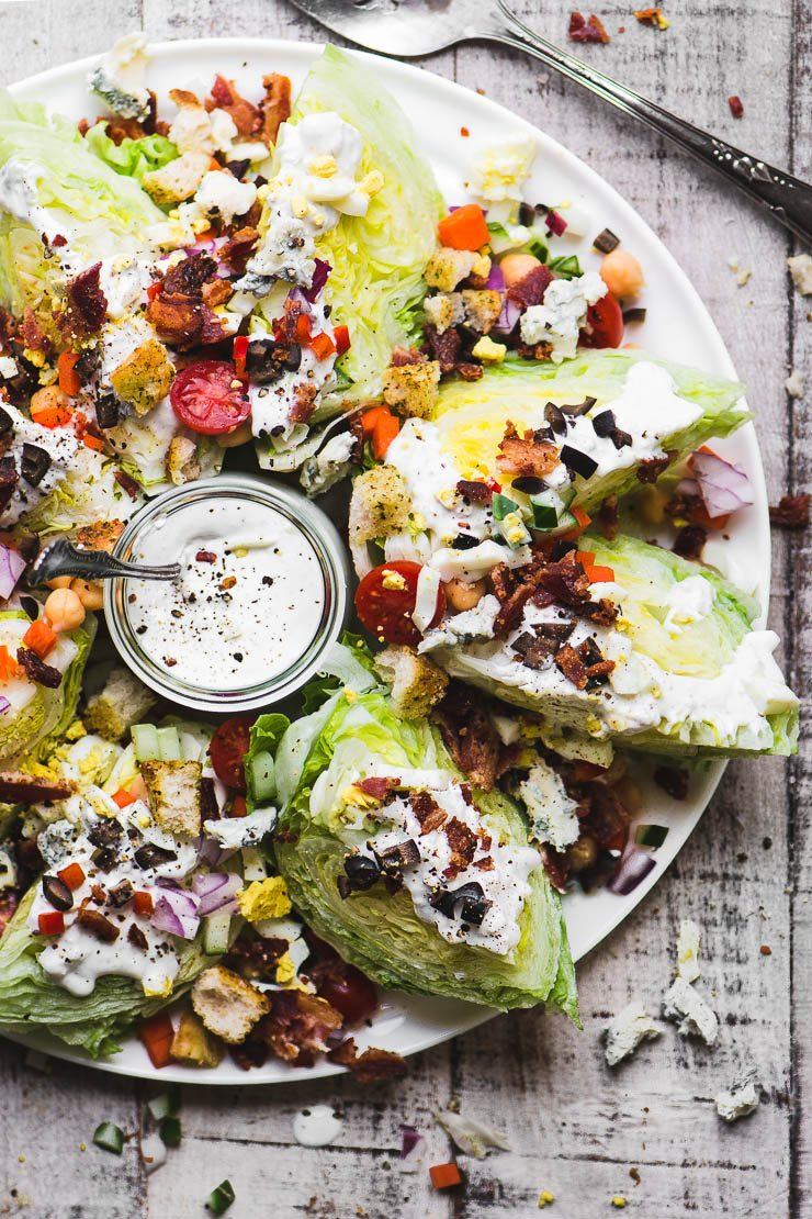 Platter of fully loaded wedge salads with blue cheese dressing