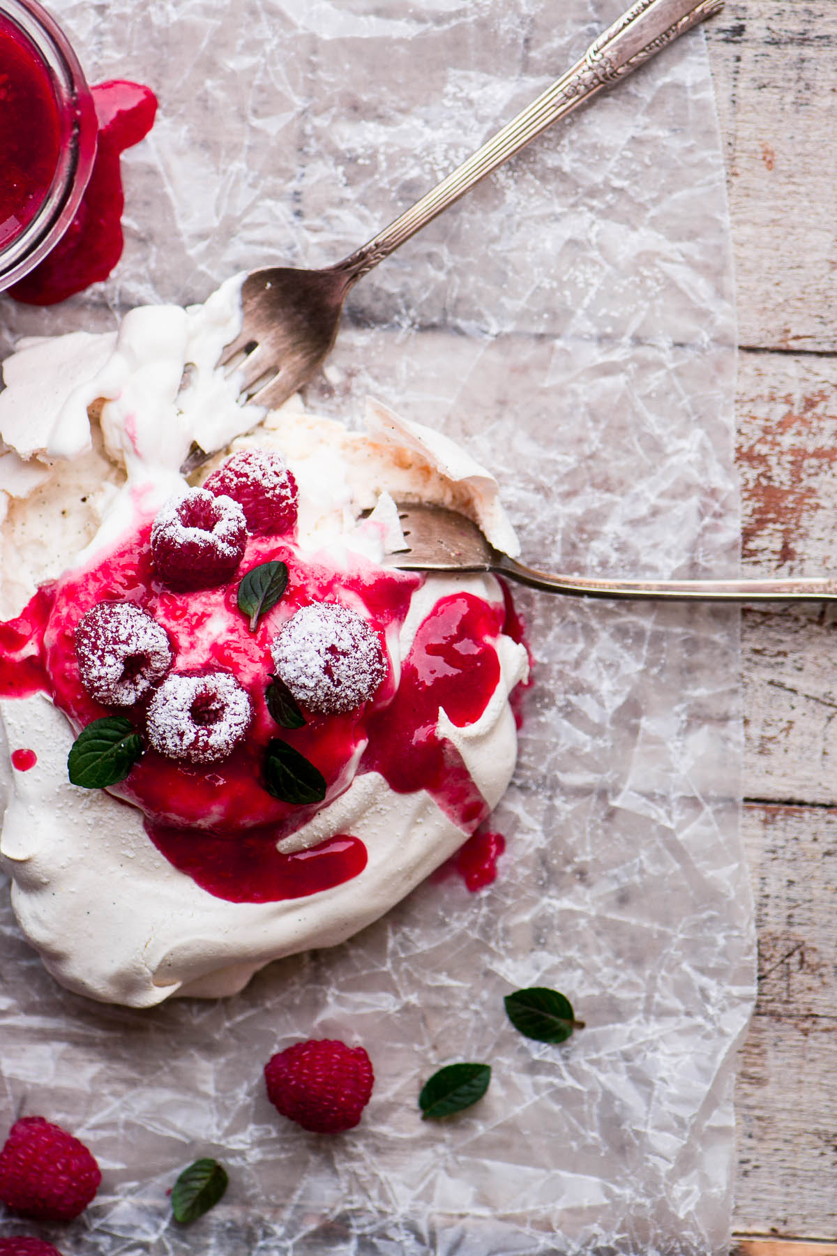 An overhead photo of an individual raspberry pavlova with whipped cream and raspberries