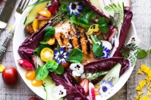 horizontal photo of grilled salmon salad with edible flowers