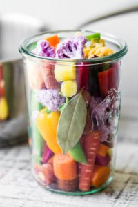 Colorful vegetables packed into a canning jar for giardiniera
