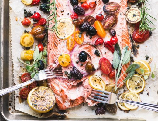 Mediterranean roasted sheet pan salmon with tomatoes, olives, onion, and lemon