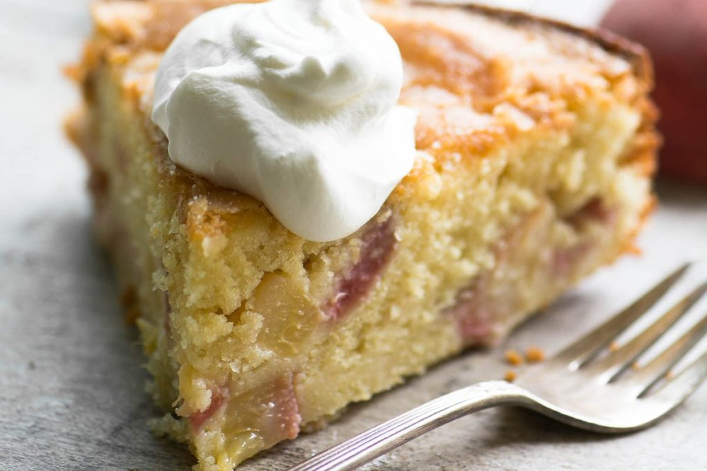 A slice of peaches and cream breakfast cake with whipped cream