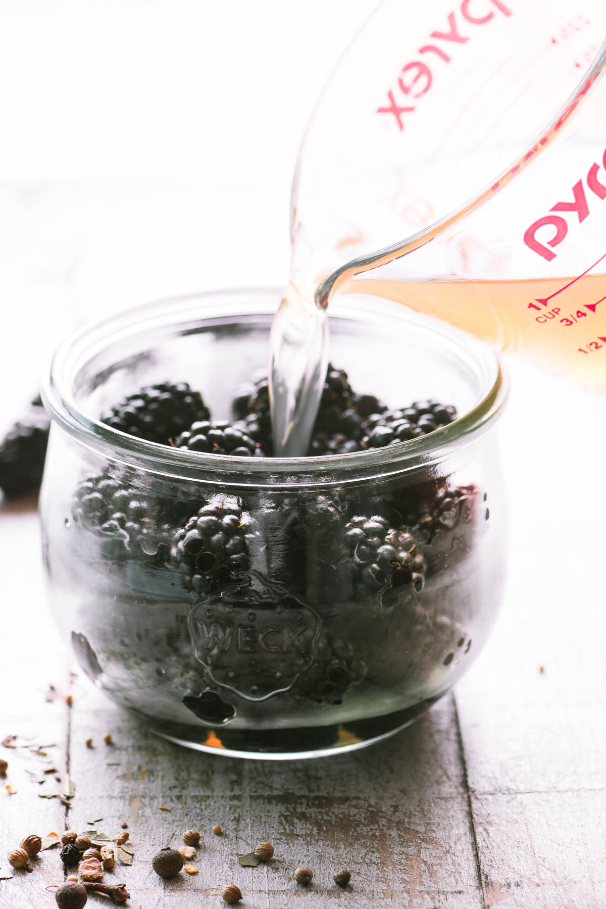 Pouring pickling brine into a jar of fresh blackberries