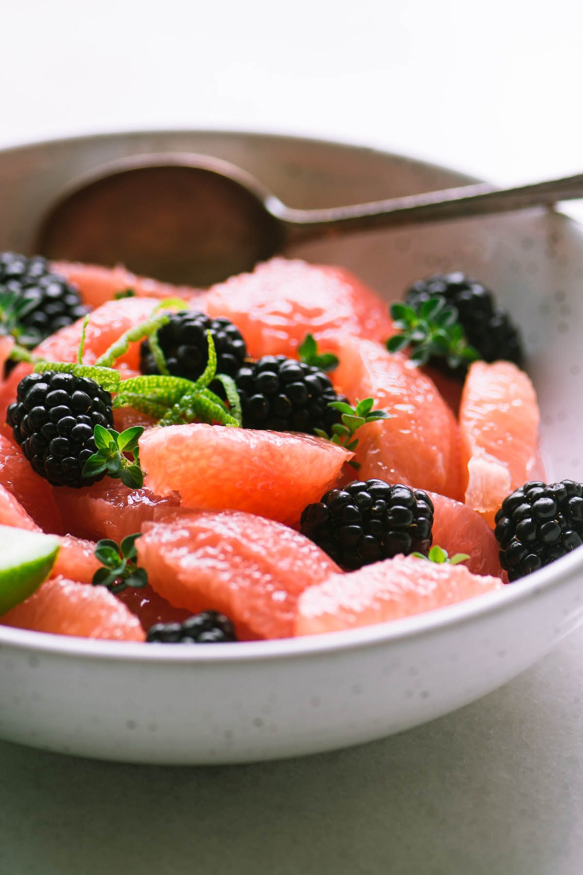 A bowl of pickled blackberry grapefruit salad with spoon