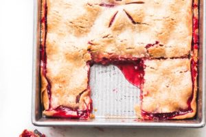 overhead photo of raspberry slab pie in the pan with piece removed