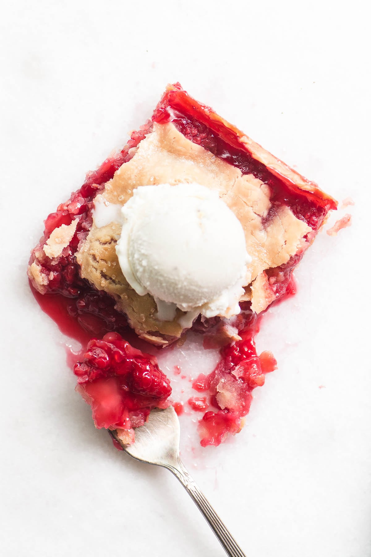 A piece of raspberry slab pie with scoop of ice cream and fork