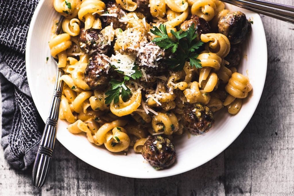 Overhead photo of a bowl of Jamie Oliver's Easy Sausage Carbonara with fork and napkin