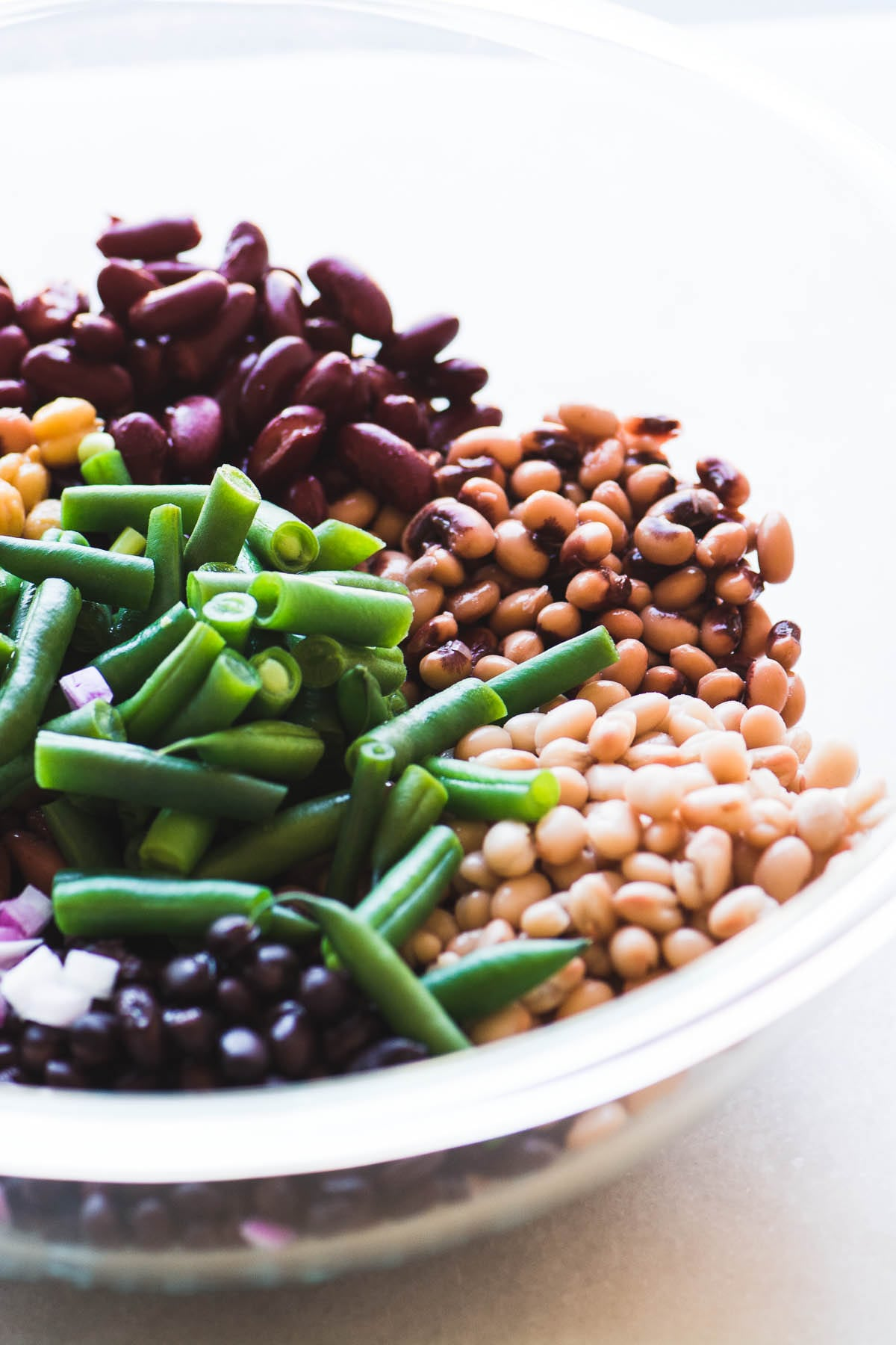Ingredients for charred corn and bean salad in a large glass bowl