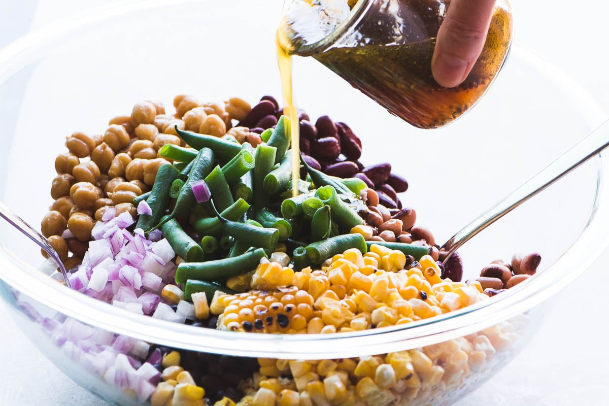 Pouring dressing onto charred corn and bean salad