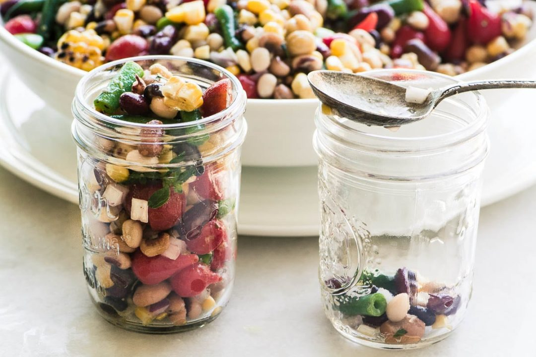 Spooning Charred Corn and Bean Salad into mason jars