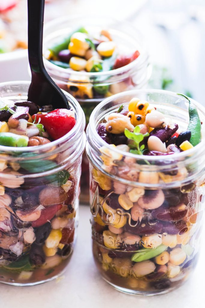 Charred corn and bean salad in mason jars, with plastic forks