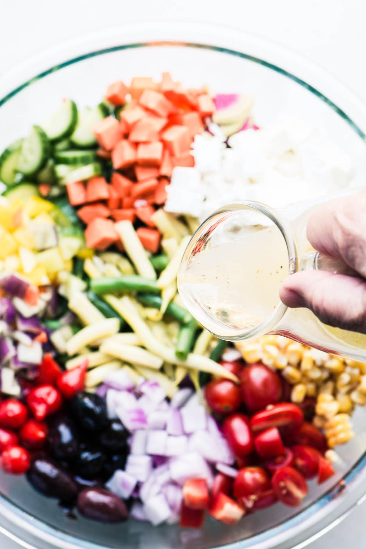 Pouring a tarragon/anchovy/lemon vinaigrette onto a farmers market vegetable salad