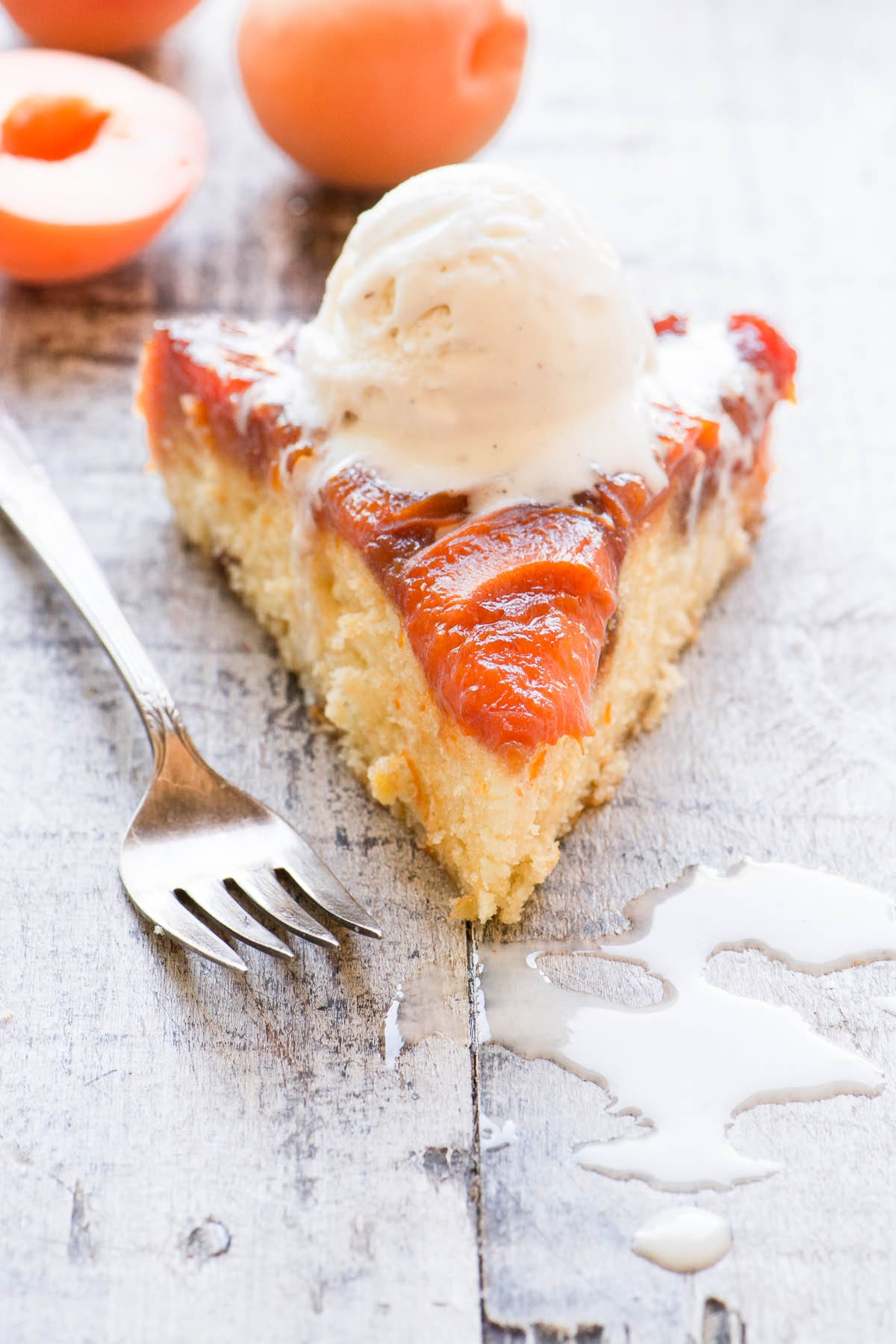 A slice of caramelized apricot cake with vanilla ice cream on a wooden surface