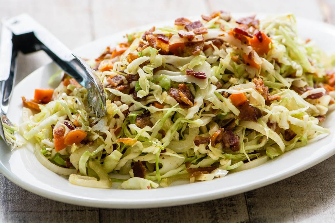 A platter of fried cabbage and bacon slaw, with tongs