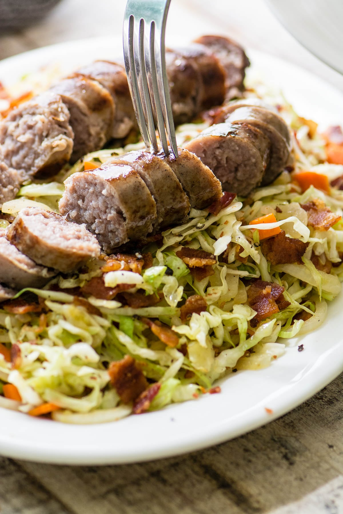 A plate of fried cabbage and bacon slaw topped with sliced brats
