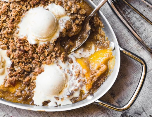 A pan of gluten free spiced peach crisp with melting ice cream