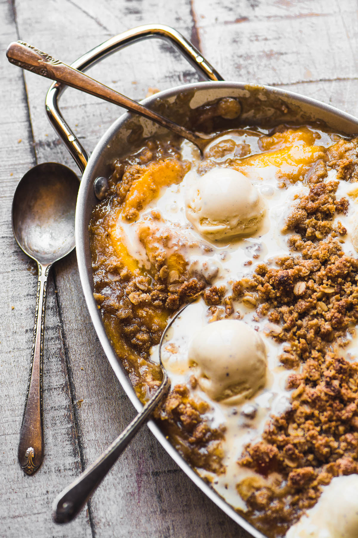 a pan of spiced peach crisp with scoops of ice cream