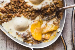 gluten free spiced peach crisp in a pan with ice cream
