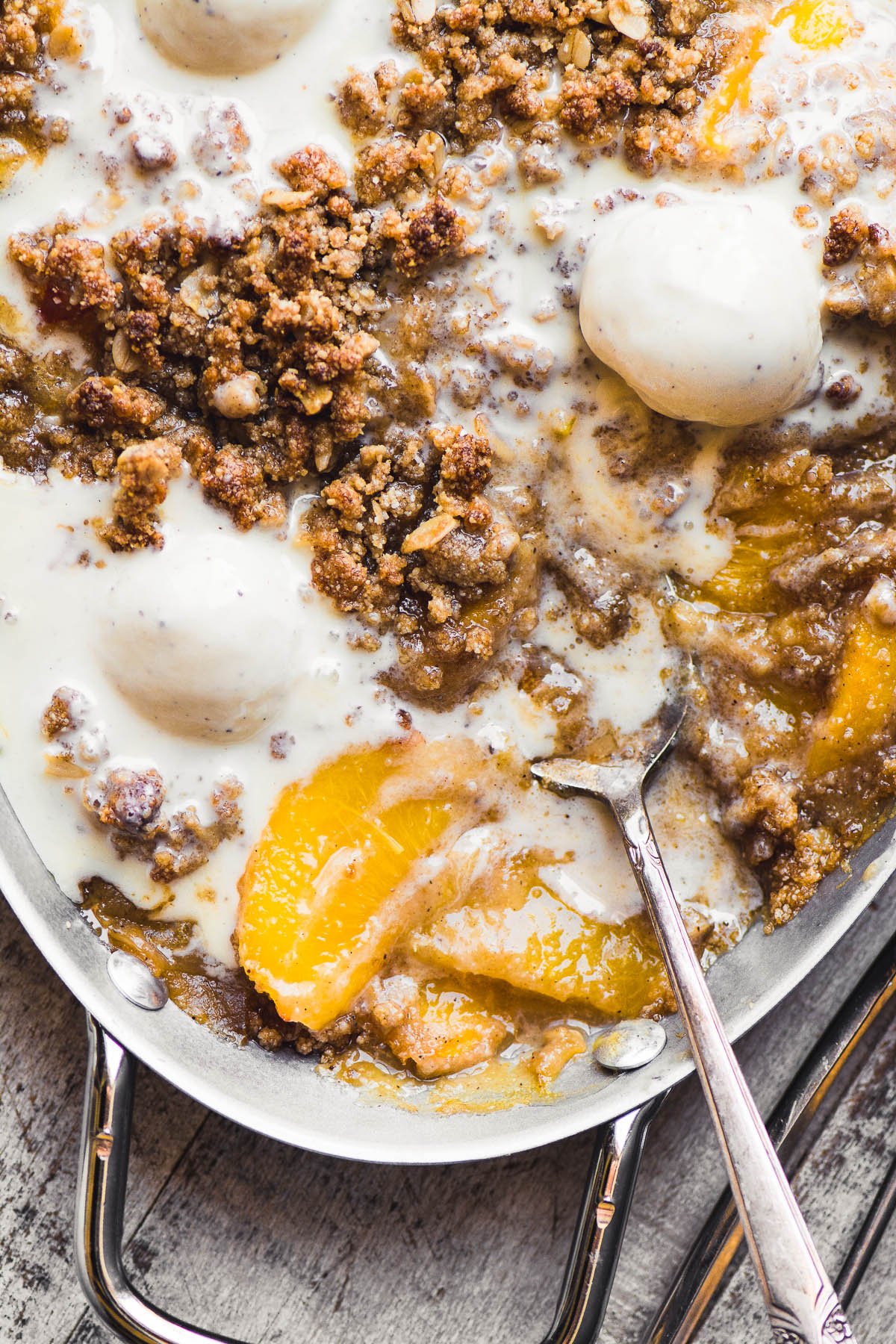gluten free spiced peach crisp in a pan with melting ice cream