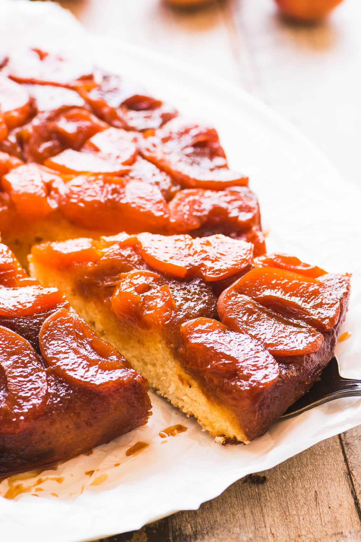 A slice being removed from a caramelized apricot upside down cake