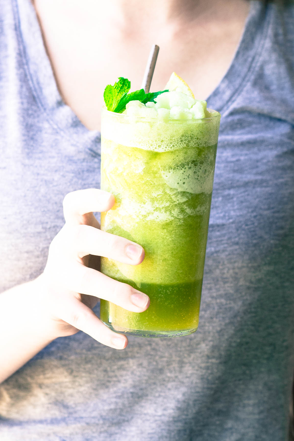 Hand holding a tall glass of Frozen Mint Lemonade, with mint sprig and straw