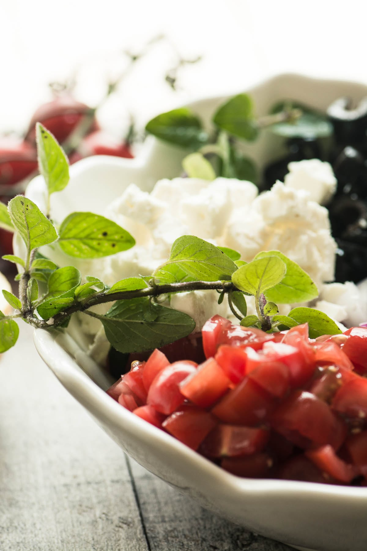 ingredients for chopped Greek salad arranged in a bowl