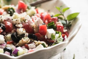 Chopped Greek Salad in a bowl with serving spoon