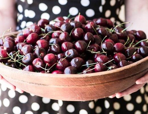 girl holding large wooden bowl of cherries