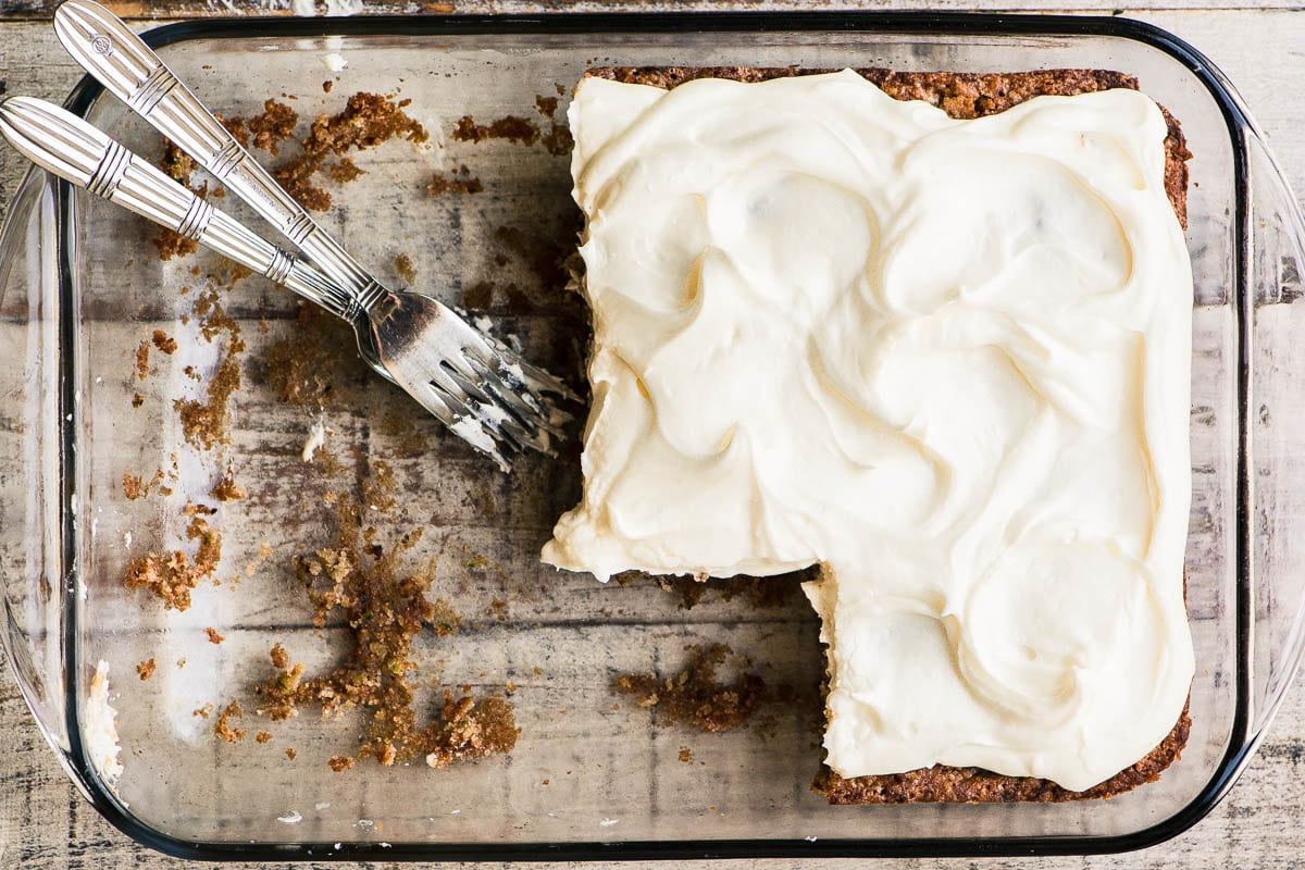 old fashioned zucchini cake with cream cheese frosting in a glass pan with forks