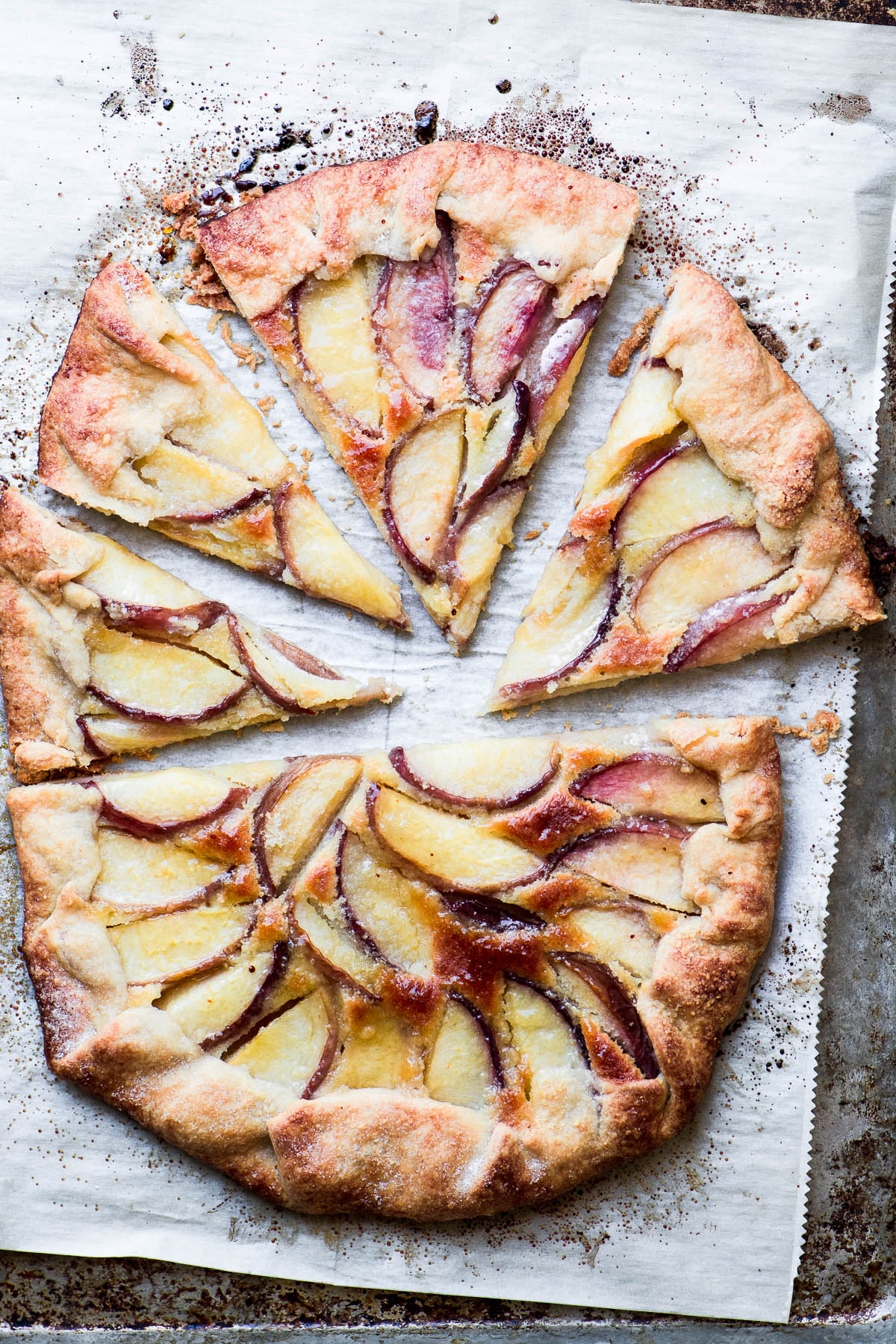 Partially sliced white peach frangipane galette on a baking sheet