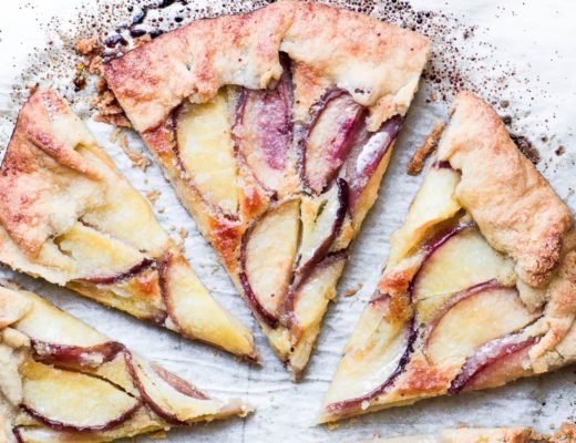 a peach frangipane galette, sliced on parchment paper