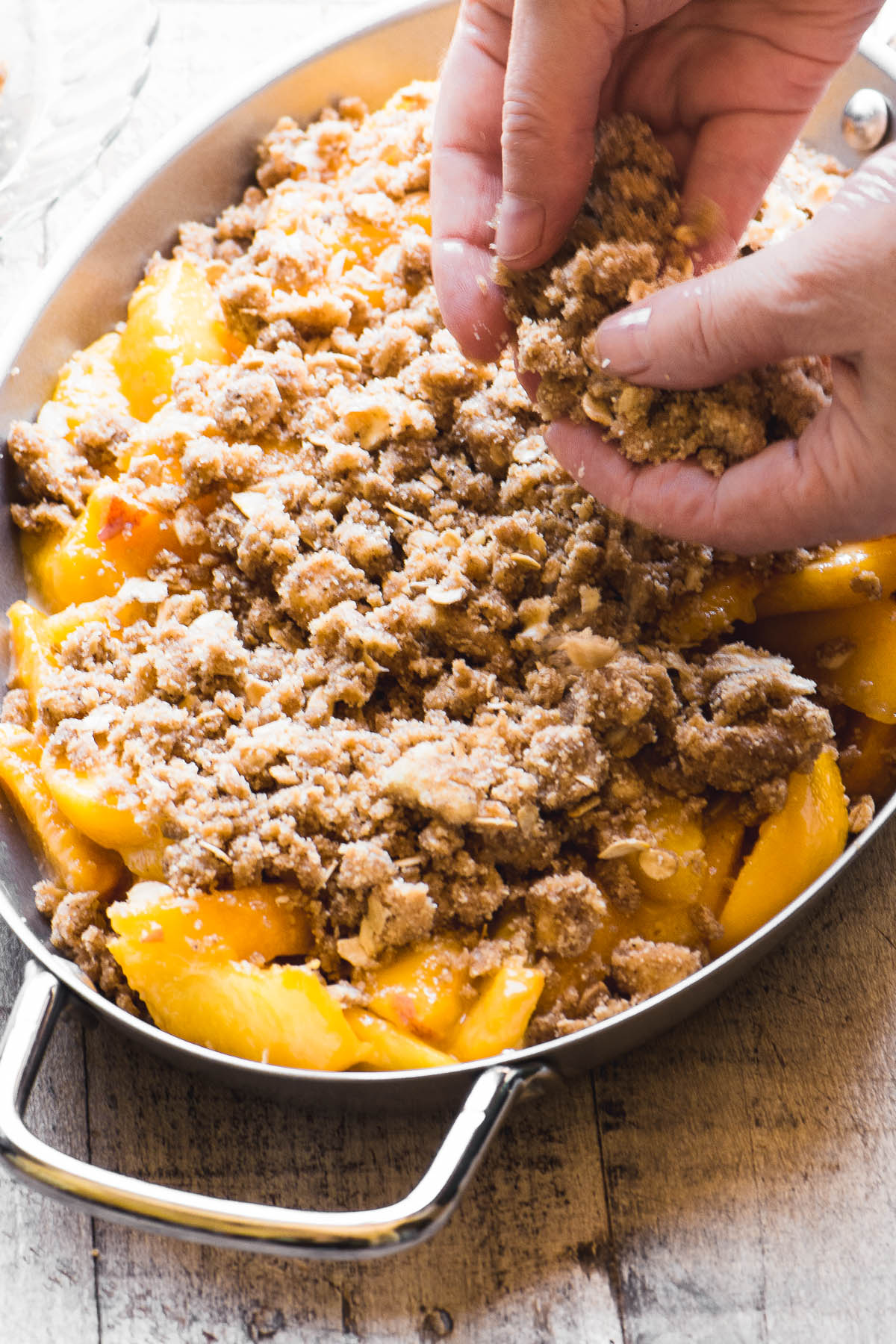Crumbling topping on a spiced peach crisp