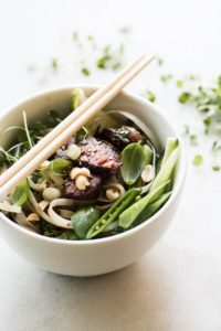 steak pad Thai salad in a bowl with chopsticks