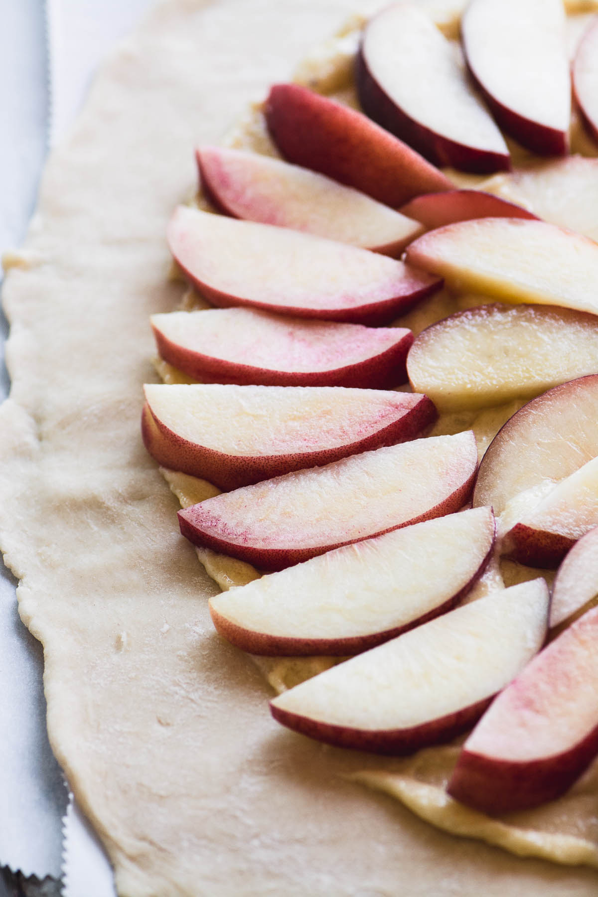 Sliced peaches on dough for White Peach Frangipane Galette