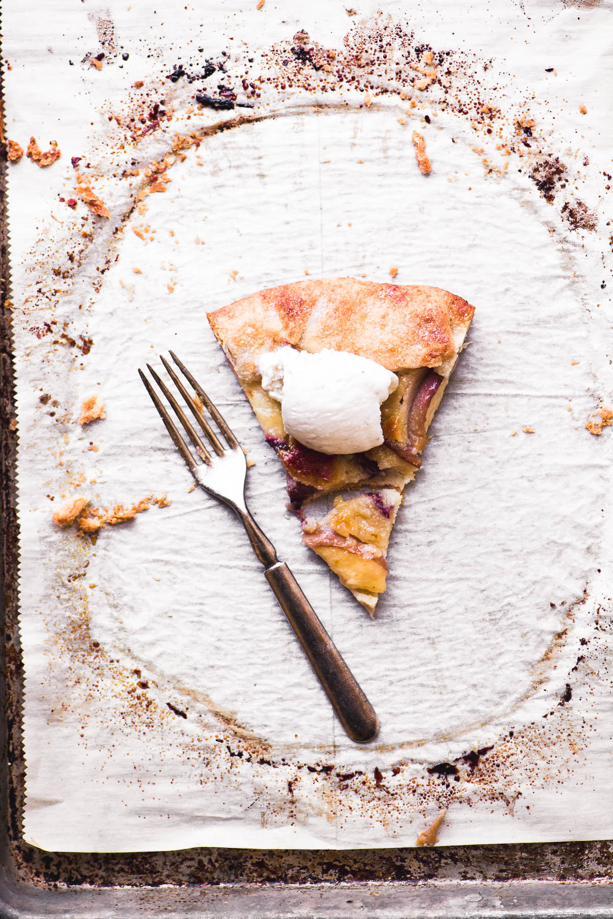 A slice of white peach frangipane galette on parchment paper with fork