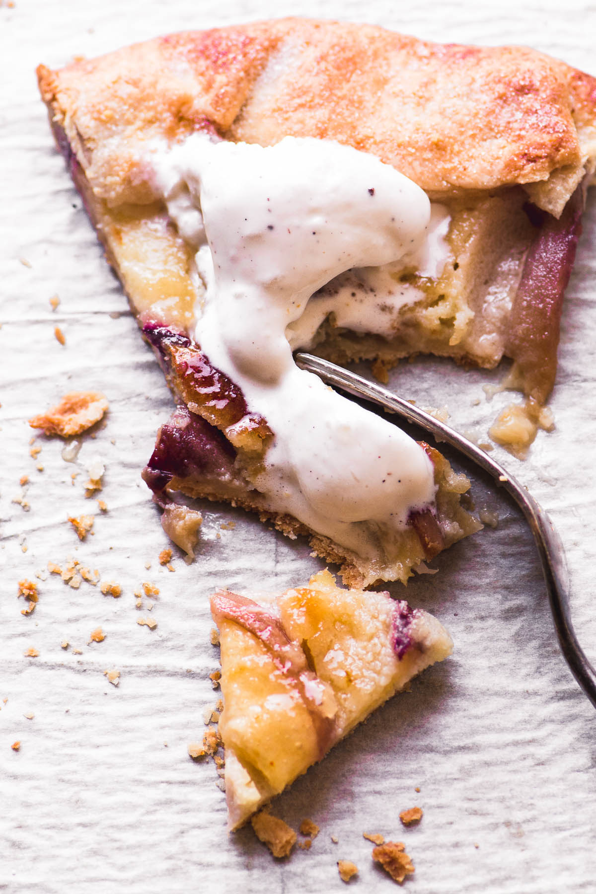A slice of white peach frangipane galette with melting ice cream and fork