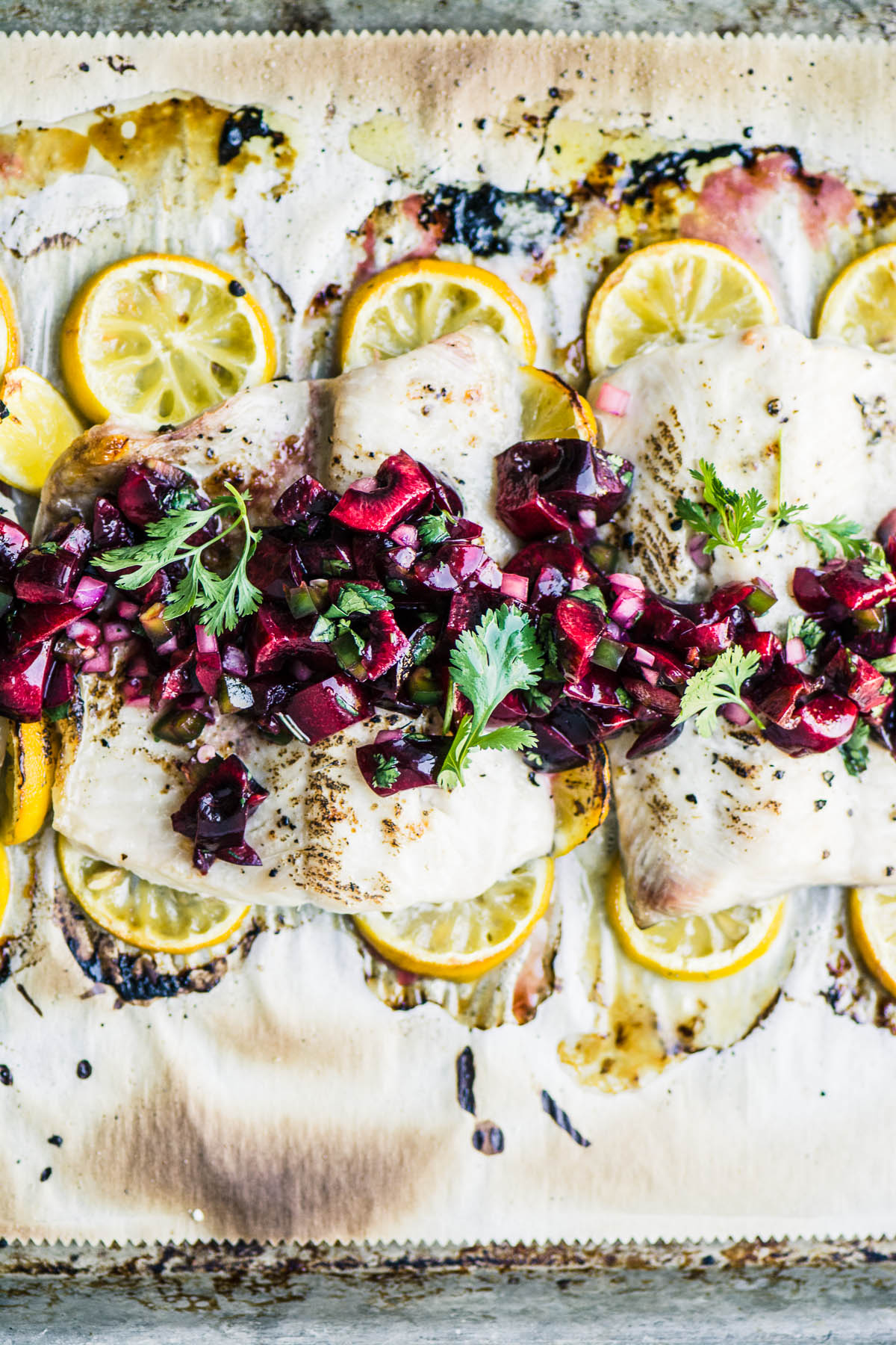 whitefish fillets topped with cherry salsa on a baking sheet with lemons