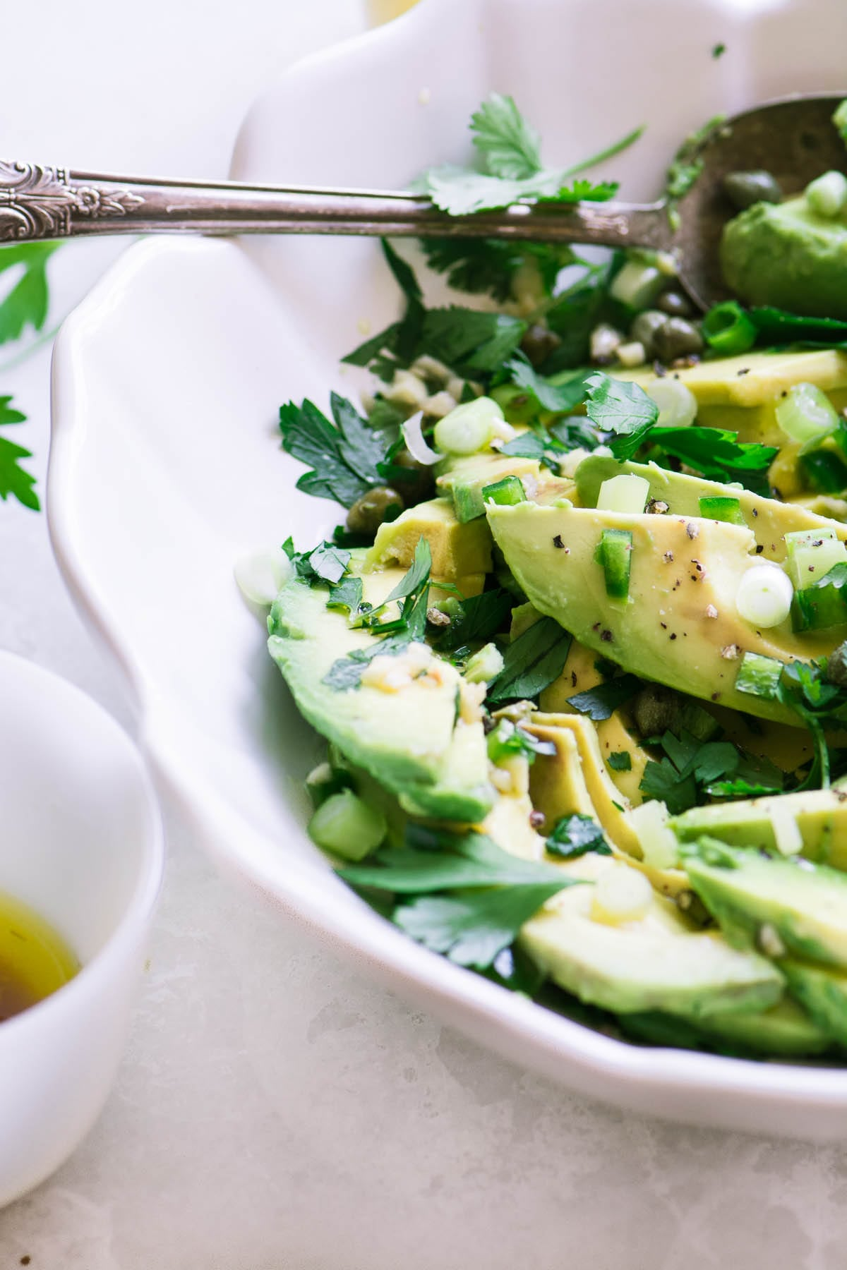 avocado and herb salad in a white bowl