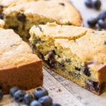 a slice of blueberry cornbread on a wooden table, with fresh blueberries