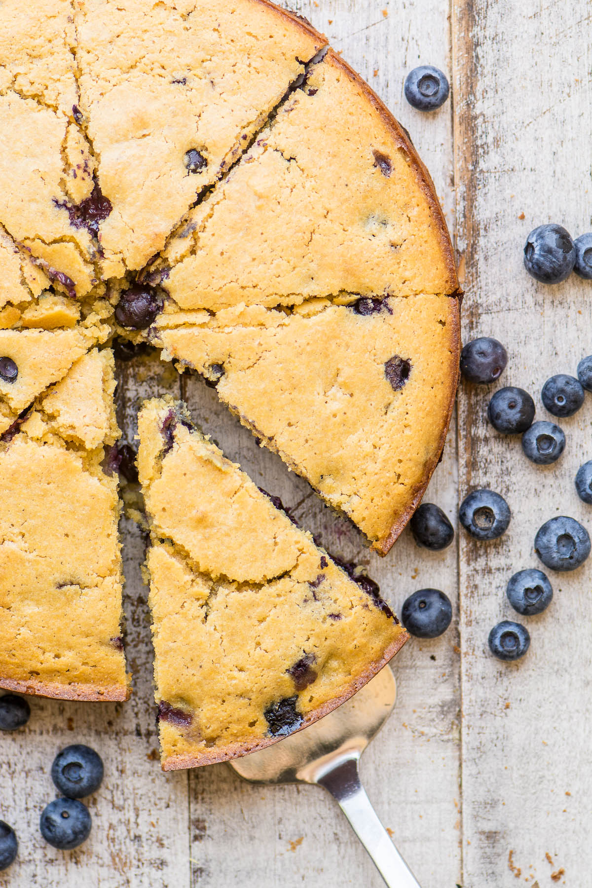 Blueberry cornbread on a wooden table with fresh blueberries